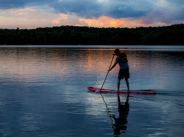 Image of a man on a paddleboard at sunset